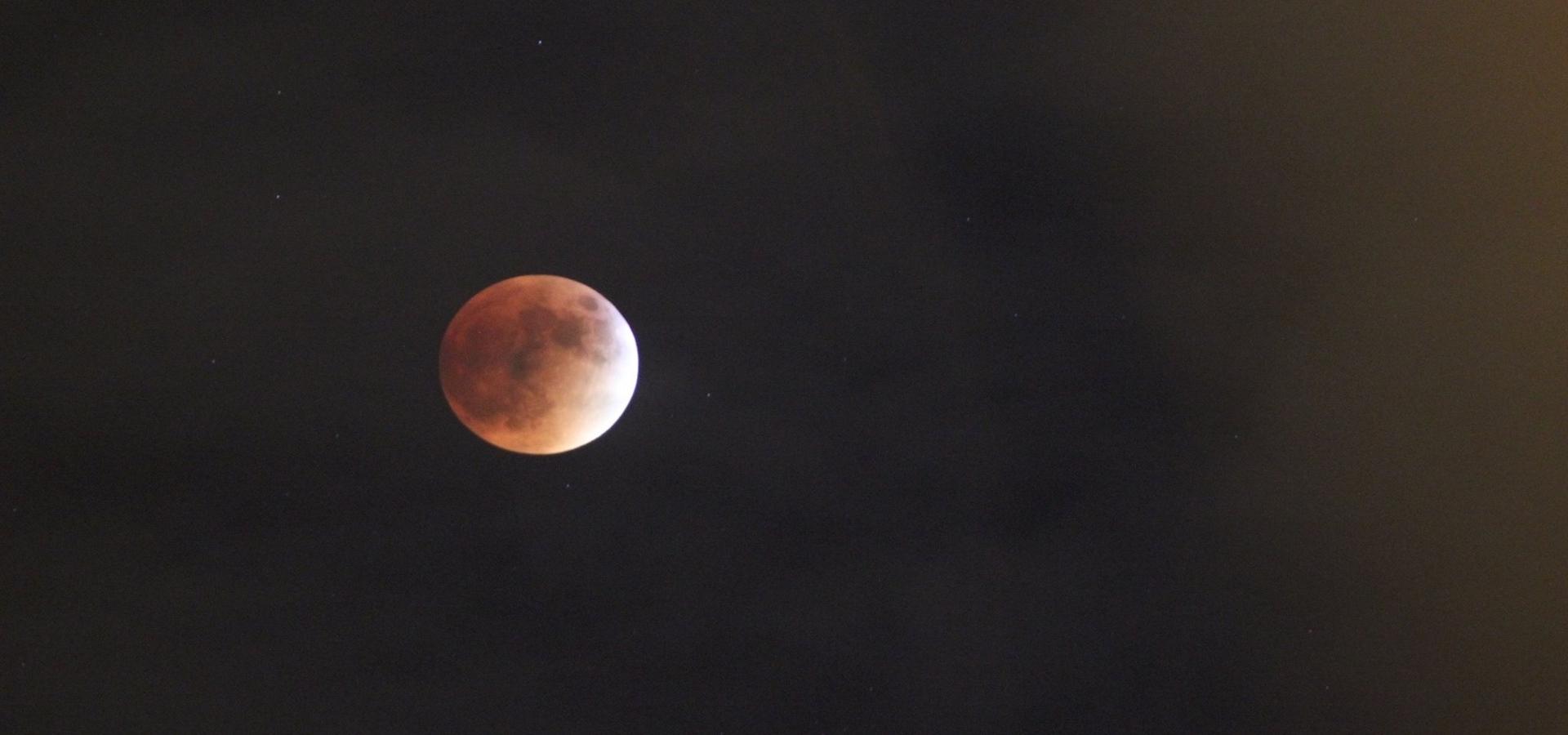 Photo of reddish moon in a black sky.