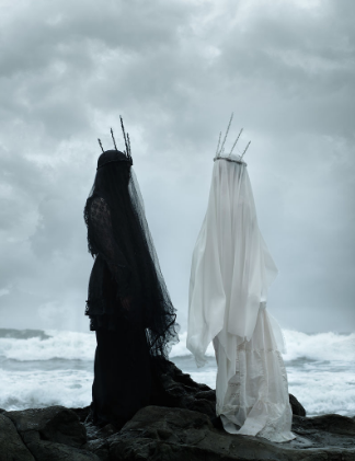 Two women face each other, shrouded (one in black, one in white) wearing minimalist, pointy crowns by the ocean..