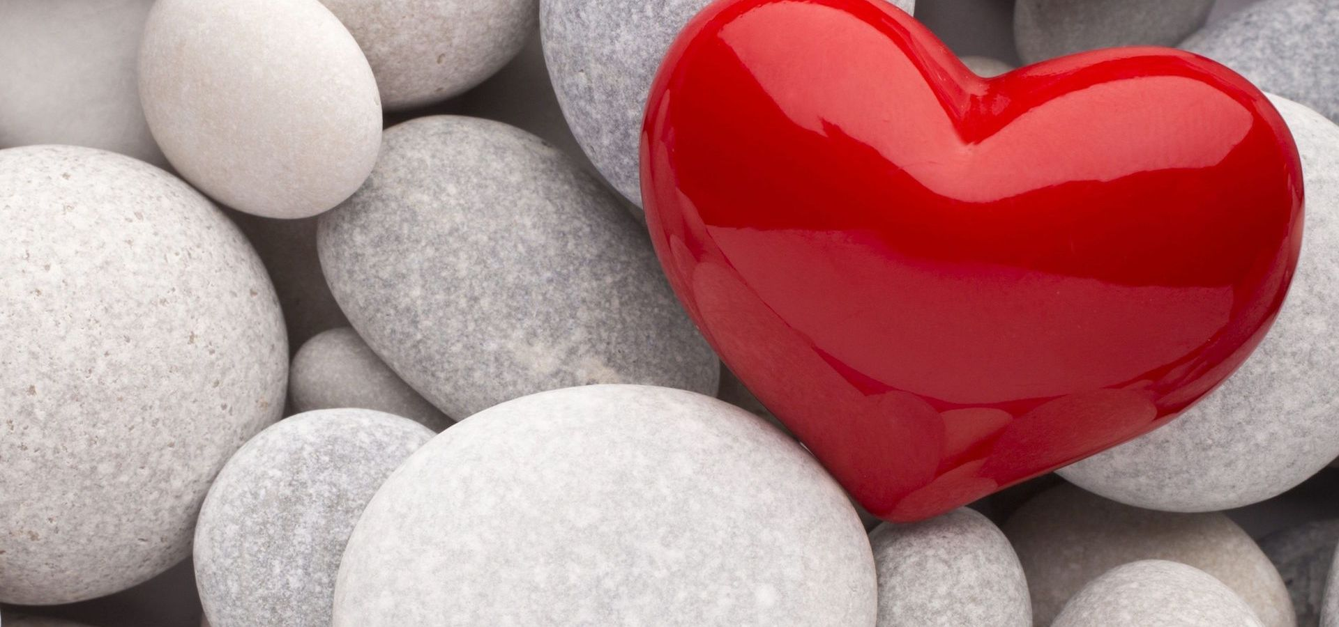Bright, red heart among light, grey stones.