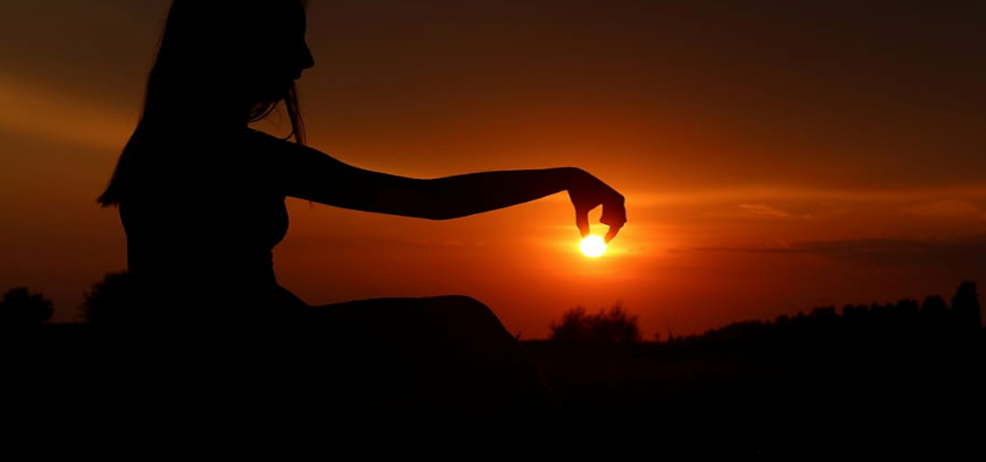 silhouette of woman holding the sun with her fingers against a dark, orange sky