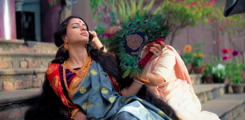 Bulbbul fanning herself as an attendant brushes her hair.