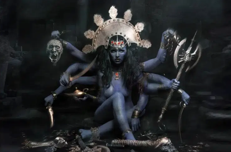 Kali facing audience in seated position, her many arms holding weapons, a genie lamp, and a decapitated head.