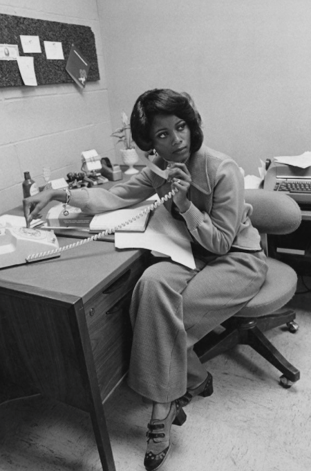 Black and white photo of young woman in 1970s, on phone at work desk.