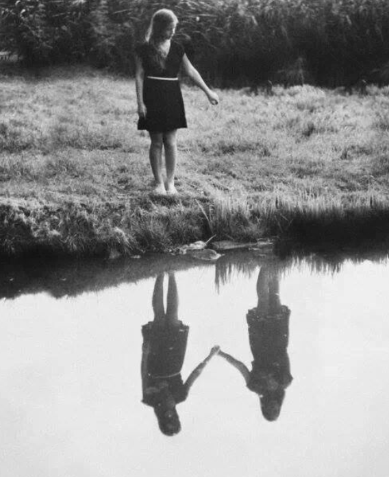 Girl standing at edge of water holding hand out. In reflection is another girl holding her hand.