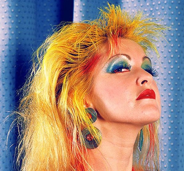 Cyndi Lauper, posing in bright makeup and hair color.